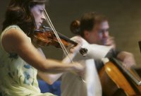 Members of the Miami String Quartet (left to right) Cathy Meng Robinson and Keith Robinson play Wednesday, July 16, 2003, at the First Presbyterian Church in DeBary. (Photo: Chad Pilster)