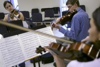 (left to right clockwise) Liz Benoit-Crew, on violin, Ryan Stauffer, on violin, and Yank'l Garcia, on viola, play Friday, July 18, 2003, during practice of the Bell South Youth Ensemble at Stetson University in DeLand. (Photo: Chad Pilster)